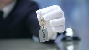 Réceptionniste montrant le keychain avec le mot de station de vacances, location de luxe de propriété, plan rapproché banque de vidéos