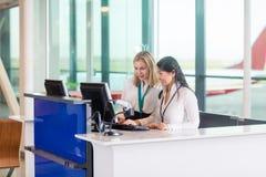 Réceptionnistes à l'aide de l'ordinateur au compteur dans l'aéroport images stock
