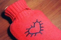 Réchauffeur élégant rouge avec le coeur images stock