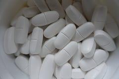 Récipient avec de grands comprimés blancs de calcium Photo stock