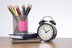Récipient avec des crayons se tenant sur des livres à côté de l'horloge Photo stock