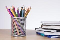 Récipient avec les crayons colorés se tenant prêt des livres Photo libre de droits