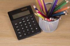 Récipient avec les crayons et la calculatrice colorés Photographie stock libre de droits