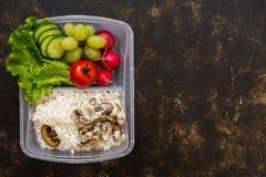 Récipient avec les légumes frais et le riz avec des champignons sur le fond de brun foncé Régime sain Vue supérieure, l'espace de photo stock