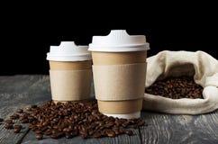 Récipient deux à utiliser une seule fois pour que les boissons chaudes emportent, sur le fond des grains de café Images libres de droits