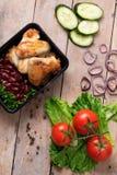 récipient en plastique avec les ailes et les légumes crus de poulet grillés sur le fond rustique photos stock
