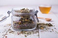 Récipient transparent avec de fines herbes sec et la tasse de thé Photo stock