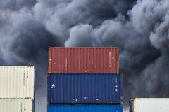 Récipients d'expédition empilés dans le stockage avec de des volutes de la fumée toxique noire d'un feu derrière photos stock