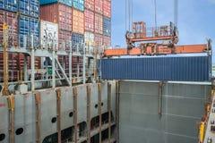 Récipients de chargement de grue de rivage dans le bateau de fret Photos stock