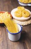 Récipients de cuisine avec des pâtes prêtes à cuisiner sur la table en bois images stock