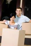 Paquets de transport de carton de couples heureux Photo stock