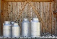 Récipients métalliques de lait sur un fond en bois affermage images stock