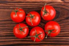 Récolte d'été des tomates rouges lumineuses avec des feuilles sur un fond en bois de brun foncé Tomates juteuses, mûres et fraîch photographie stock