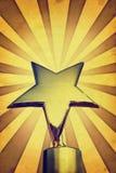 Récompense d'or d'étoile de vintage sur la position contre le jaune Image stock
