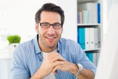 Rédacteur fonctionnant à son ordinateur souriant à l'appareil-photo Image stock