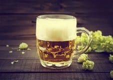 Rédigez la bière froide dans le pot en verre avec le houblon en cônes mûr vert sur le noir Photos libres de droits