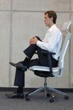 Réduction du stress dans le travail de bureau - équipez l'exercice sur la chaise Photographie stock