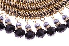 Réduisez le collier en fragments avec les perles noires sur un fond blanc Images stock