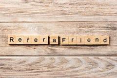 Référez-vous un mot d'ami écrit sur le bloc en bois référez-vous un texte d'ami sur la table, concept images stock