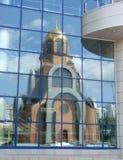 Réflexion d'église dans les hublots d'une construction moderne Photographie stock