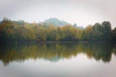 Réflexion d'arbres et de lac de chute un matin brumeux Photos libres de droits