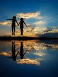 Réflexion d'heureux de deux femmes sautant et de silhouette de coucher du soleil Photos stock