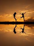 Réflexion d'heureux de deux femmes sautant et de silhouette de coucher du soleil Images stock