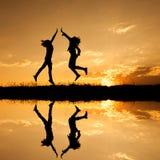 Réflexion d'heureux de deux femmes sautant et de silhouette de coucher du soleil Photos libres de droits
