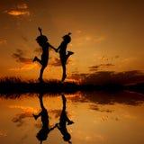 Réflexion d'heureux de deux femmes sautant et de silhouette de coucher du soleil Photographie stock