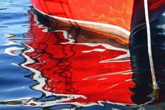 Réflexion d'un bateau à rames rouge Photo stock