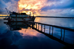 Réflexion d'un bateau sur le voir avec le coucher du soleil photographie stock