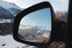 Réflexion d'un beau paysage de montagne au coucher du soleil dans le miroir latéral de la vue arrière Images libres de droits
