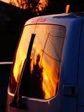 Réflexion d'un coucher du soleil dans la fenêtre arrière d'un fourgon images libres de droits