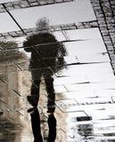 Réflexion d'un homme en trottoir pluvieux de trottoir Image stock