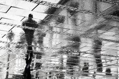 Réflexion d'un homme en trottoir pluvieux de trottoir Images stock