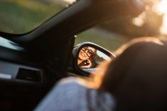 Réflexion d'une jeune fille aux cheveux foncés de sourire dans des lunettes de soleil dans un miroir latéral d'une voiture images libres de droits