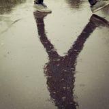 Réflexion dans l'asphalte humide Adolescent de marche Photographie stock