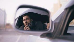 Réflexion dans le miroir latéral du jeune homme de détective privé s'asseyant à l'intérieur de la voiture et photographiant avec  photo libre de droits