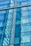 Réflexion dans le mur de verre bleu de l'immeuble de bureaux moderne Image libre de droits