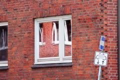 Réflexion dans une fenêtre sur un mur de briques rouge Image libre de droits