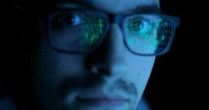 Réflexion de code de données dans les programmeurs, verres de pirates informatiques L'homme regarde l'appareil-photo banque de vidéos