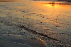Réflexion de coucher du soleil outre des eaux de marée basse Images stock