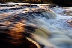 Réflexion de coucher du soleil sur la cascade à écriture ligne par ligne Photo stock