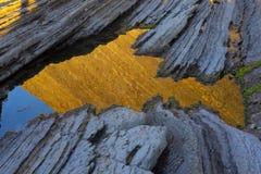 Réflexion de flysch de Zumaia dans l'eau de la mer Images libres de droits