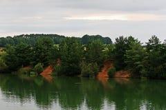 Réflexion de frontière d'arbres au lac Photographie stock