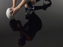 Réflexion de joueur sur un genou avec la boule de rugby Photographie stock libre de droits