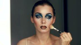 Réflexion de la jeune belle fille appliquant son maquillage d'art, regardant dans un miroir banque de vidéos
