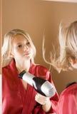 Réflexion de la jeune femme de blone utilisant le sèche-cheveux Images libres de droits