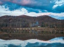 Réflexion de lac au coucher du soleil avec Pier Dock Foot Path photos stock
