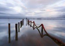 Réflexion de lac au-dessus du dock submergé au coucher du soleil photos stock